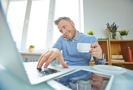 work addicted: Businessman with coffee working on laptop and speaking on cellphone in office