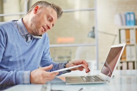 work addicted: Young businessman or agent typing and speaking on cellphone Stock Photo