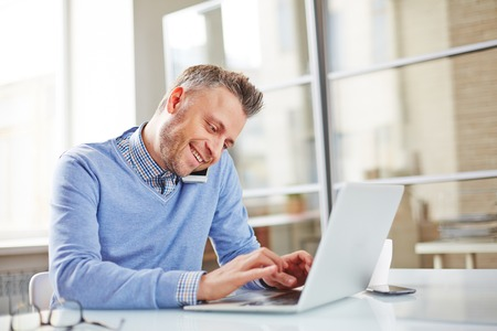 work addicted: Happy manager typing and phoning
