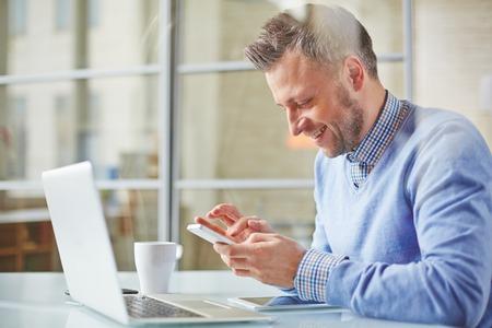 empleados trabajando: Sms escritura gerente felices en la oficina
