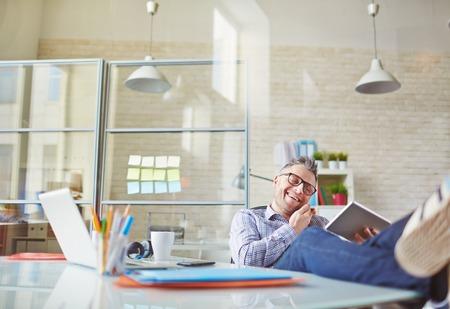 work addicted: Cheerful man using modern technologies in office