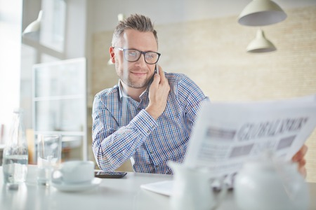 newspaper: Confident businessman in eyeglasses talking on cellphone while reading newspaper Stock Photo