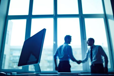 personas saludandose: Monitor de la computadora en lugar de trabajo con dos hombres de negocios apret�n de manos en el fondo Foto de archivo