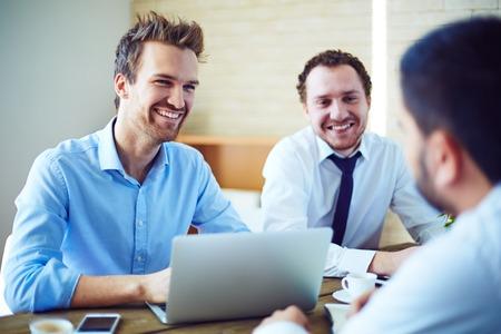 entrevista de trabajo: Hombres de negocios alegre que escucha candidato para la vacante