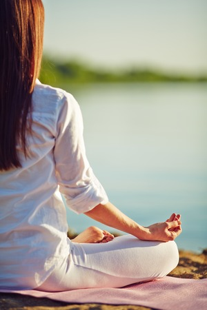 meditating woman: Meditating woman relaxing on coastline Stock Photo
