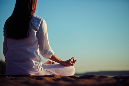 Back of peaceful woman meditating outside