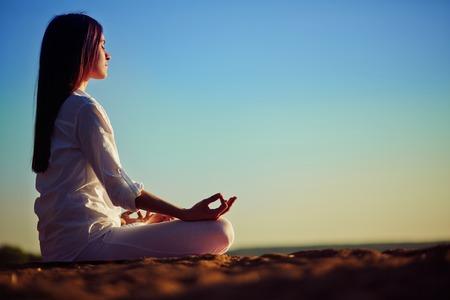 ビーチで瞑想静かな若い女性