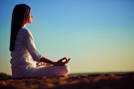 Tranquil young woman meditating on the beach