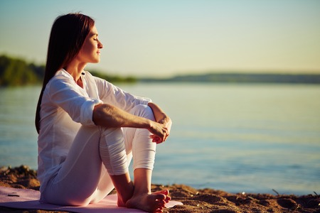 harmony: Tranquil young woman sitting on the beach Stock Photo