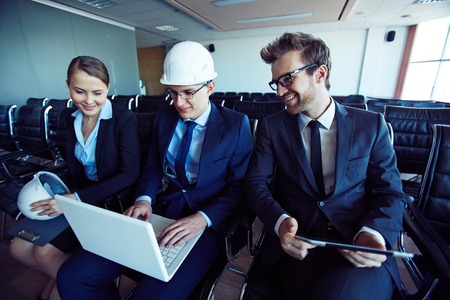 executive helmet: Group of young architects looking through electronic data Stock Photo