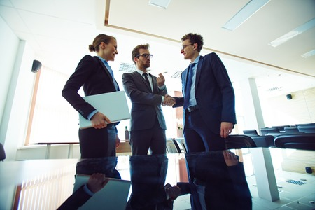 handshaking: Male colleagues handshaking with young businesswoman near by