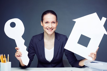 Cheerful businesswoman with paper house and key photo