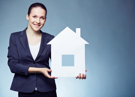 Cheerful female realtor showing paper house photo