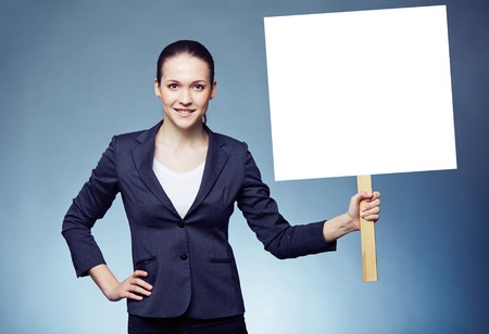 Serious businesswoman with blank paper ad photo