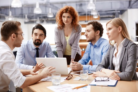 colleague: Group of business partners listening to colleague at meeting