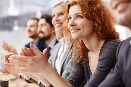 Smiling female applauding at conference between her colleagues Imagens