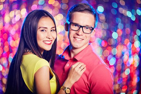 amorous: Amorous young couple looking at camera while enjoying party