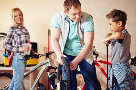 pumping: Little boy pumping bicycle wheel with his father helping him Stock Photo