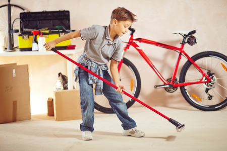 lad: Cute lad doing cleanup in garage