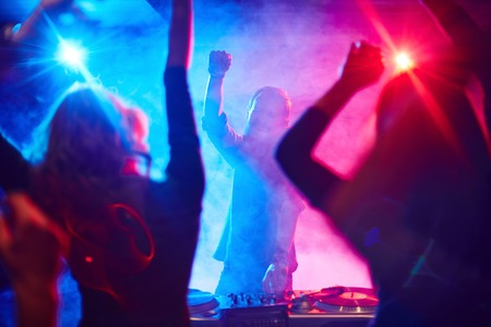 Excited deejay and dancing crowd enjoying disco party in nightclub photo