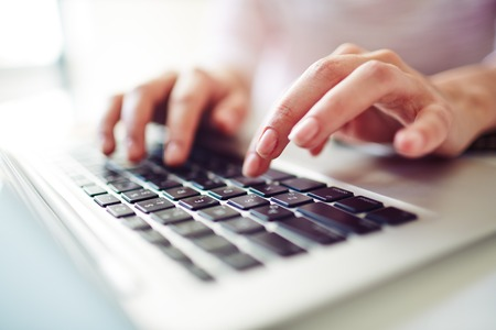 Fingers touching buttons of laptop keypad photo