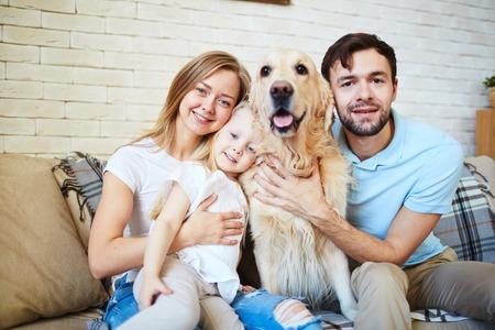 Familia moderna y su mascota lindo descansando en su casa Foto de archivo