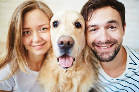 amorous woman: Happy young couple and their pet looking at camera Stock Photo