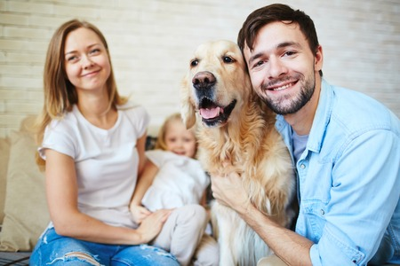 man dog: Young man embracing dog with happy woman and girl on background