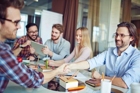 handshaking: Businessmen handshaking on background of working team