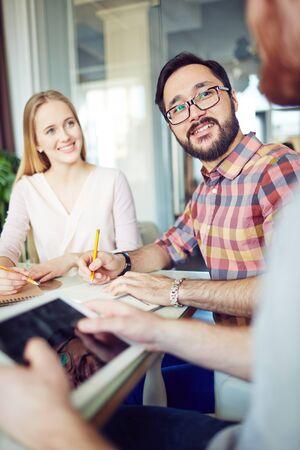 ejecutivo en oficina: Dos j�venes directivos anotando ideas de su colega