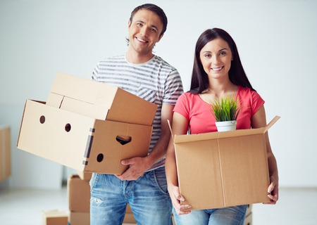 Couple of young settlers holding boxes Stock Photo