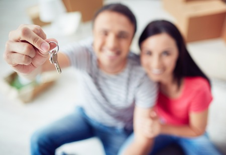 key: Young couple showing key from new apartment