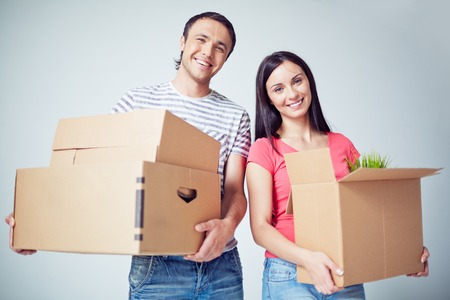 house wife: Happy young couple with boxes looking at camera