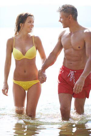 wet bikini: Amorous couple in swimwear walking in water Stock Photo