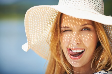 flirty: Flirty girl in sunhat winking and looking at camera