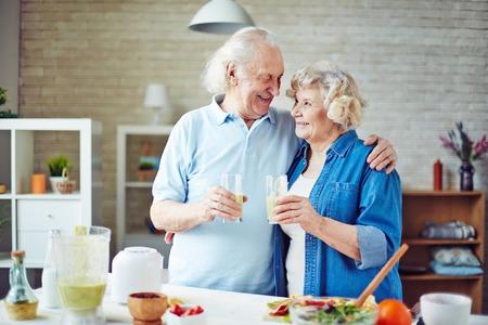 parejas felices: Animando la tercera edad con vasos de batido fresco Foto de archivo