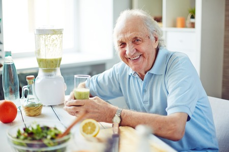 Senior man with glass of fruit smoothie sitting in kitchen photo