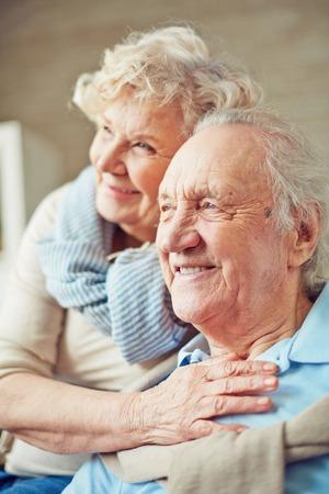 高齢者の女性が彼女の夫を抱きしめる