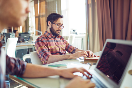 hombre de negocios: Joven empresario sentado por el lugar de trabajo en la oficina