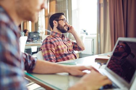 llamando: Joven empresario sentado por el lugar de trabajo y hablando en el teléfono