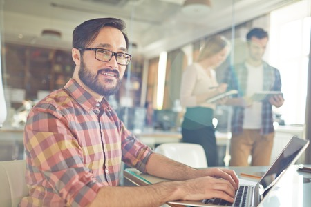 information technology: Handsome office worker typing by workplace