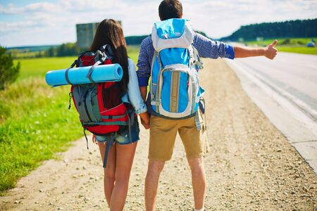 rucksacks: Young man and woman with rucksacks hitch-hiking by road