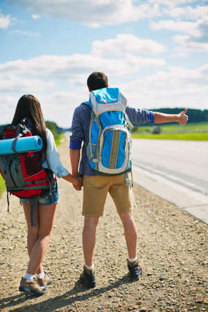 hitchhiking: Rear view of hitch-hiking couple with rucksacks Stock Photo
