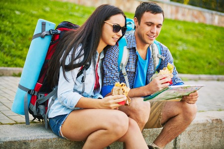 rucksacks: Young man and woman with rucksacks and map choosing travel route