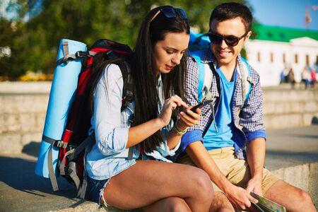 adventure travel: Young couple with rucksacks consulting mobile navigator Stock Photo