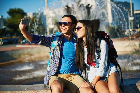 rucksacks: Affectionate couple with rucksacks making selfie on background of fountain Stock Photo