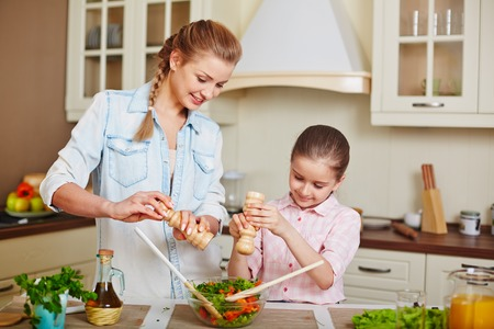 healthy girls: Cute girl and her mother adding salt or spices into bowl with fresh vegetable salad Stock Photo