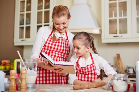 kitchen aprons: Cute girl and her mother reading how to make dough at home