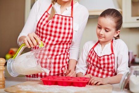 filling in: Curious girl looking at her mother filling in muffin forms with liquid dough Stock Photo
