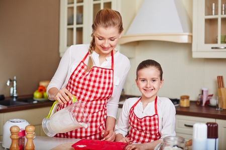 filling in: Adorable girl and her mother filling in muffin forms with liquid dough near by Stock Photo